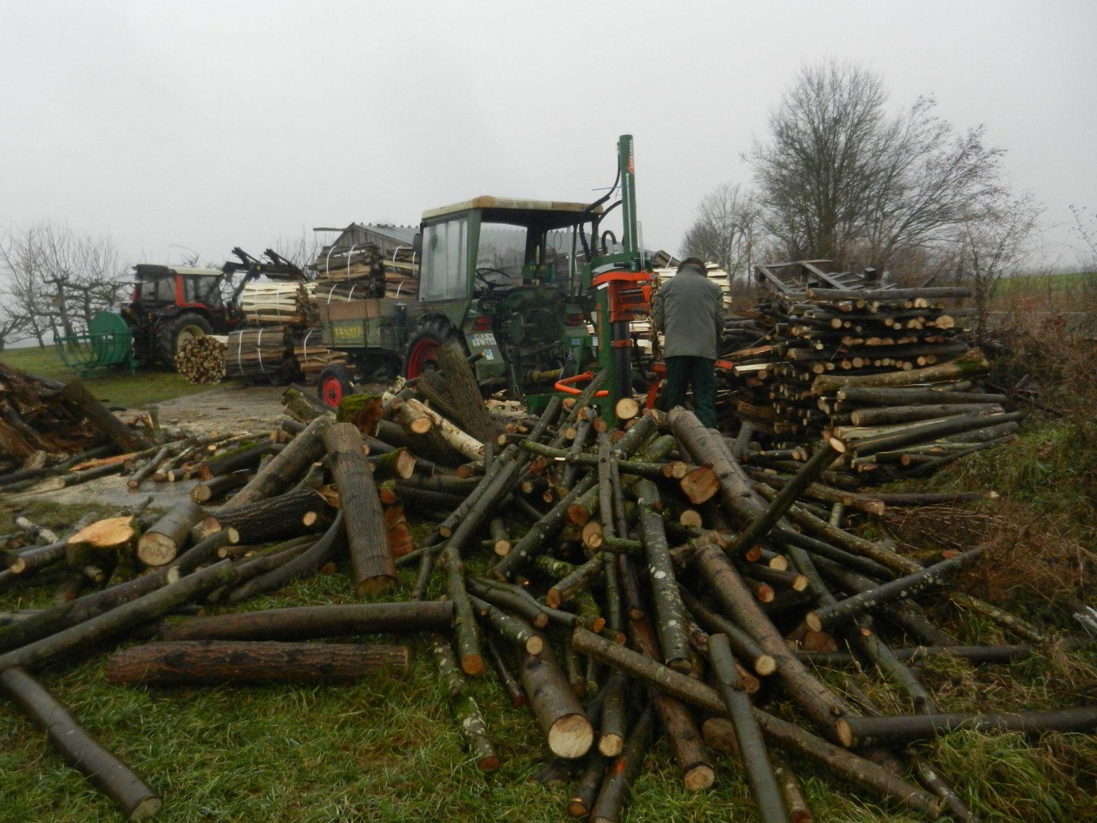 Traktor mit Holzspalter mit arbeitender Person. Haufen mit losem Holz im Vordergrund und Stapel mit fertig gespaltenen Scheiten im Hintergrund